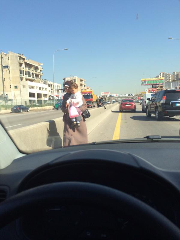 امرأة مع طفلها تحاول تجاوز الأوتوستراد
